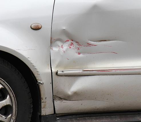 Red scratch on silver car door exterior